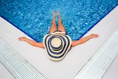 Γυναίκα στη χαλαρώνοντας πισίνα καπέλων αχύρου στοκ εικόνες με δικαίωμα ελεύθερης χρήσης