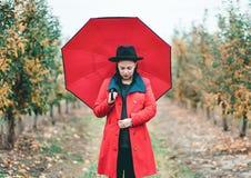 Γυναίκα στο κόκκινο παλτό και με την ομπρέλα μεταξύ των δέντρων στον κήπο μήλων στην εποχή φθινοπώρου Όμορφο πορτρέτο του καυκάσι στοκ εικόνες