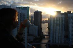 Γυναίκα στο μπουρνούζι που πίνει τον καφέ ή το τσάι πρωινού της σε ένα στο κέντρο της πόλης μπαλκόνι Όμορφη ανατολή στο στο κέντρ στοκ εικόνα
