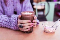 Γυναίκα στο παχύ ιώδες freshly-made κακάο κατανάλωσης πουλόβερ στοκ φωτογραφία με δικαίωμα ελεύθερης χρήσης