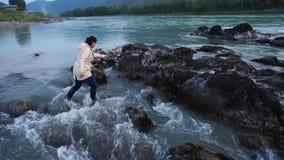 Γυναίκα στο πεζοπορώ που περπατά μέσα στο νερό στον απότομο βράχο απόθεμα βίντεο