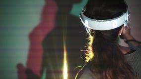 Γυναίκα πορτρέτου στην κάσκα VR με τις χρωματισμένες σκιές στο υπόβαθρο φιλμ μικρού μήκους