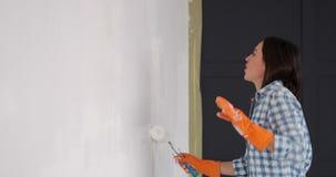 Γυναίκα που έχει τη διασκέδαση χρωματίζοντας τον τοίχο με έναν κύλινδρο φιλμ μικρού μήκους