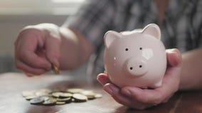 Γυναίκα που βάζει το νόμισμα στη piggy τράπεζα, που σώζει την έννοια χρημάτων Η μελλοντική εκπαίδευση δανείου αναγκών ή η πίστωση φιλμ μικρού μήκους