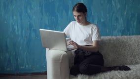 Γυναίκα που εργάζεται στο φορητό προσωπικό υπολογιστή καθμένος στον καναπέ στο δωμάτιο απόθεμα βίντεο