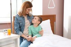 Γυναίκα που επισκέπτεται την λίγο παιδί με την ενδοφλέβια σταλαγματιά στοκ φωτογραφία