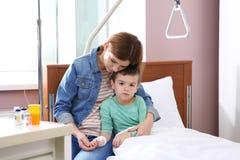 Γυναίκα που επισκέπτεται την λίγο παιδί με την ενδοφλέβια σταλαγματιά στοκ εικόνα