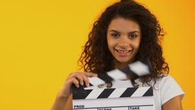 Γυναίκα που κλείνει το μάτι και που χρησιμοποιεί clapper τον πίνακα, που γυρίζει τη θετική ταινία, παραγωγή κινηματογράφων απόθεμα βίντεο