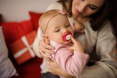 Γυναίκα που κρατά την κόρη της με το τόξο στο κεφάλι σε ετοιμότητα στοκ εικόνα