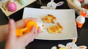 Γυναίκα που διακοσμεί τα μπισκότα Πάσχας με την κρέμα απόθεμα βίντεο