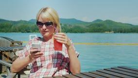 Γυναίκα που στηρίζεται σε μια θερινή περιοχή στον καφέ Χρησιμοποιεί το τηλέφωνο Στο υπόβαθρο, τη λίμνη και τα βουνά Θέρετρο μέσα φιλμ μικρού μήκους