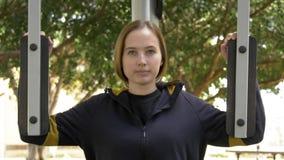 Γυναίκα που τελειώνει τα excercises της που χρησιμοποιούν τον εκπαιδευτή οδών φιλμ μικρού μήκους