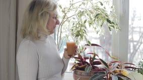 Γυναίκα που φαίνεται έξω το παράθυρο και ο χυμός κατανάλωσης απόθεμα βίντεο
