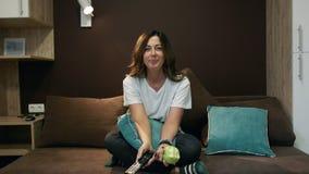 Γυναίκα που προσέχει τη TV και που τρώει τη Apple που κάθεται στο κρεβάτι στην κρεβατοκάμαρα Κανάλια διακοπτών με τον τηλεχειρισμ φιλμ μικρού μήκους