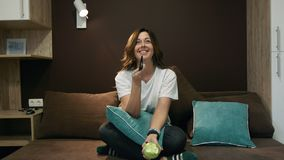 Γυναίκα που προσέχει τη TV και που τρώει τη Apple που κάθεται στο κρεβάτι στην κρεβατοκάμαρα Κανάλια διακοπτών με τον τηλεχειρισμ απόθεμα βίντεο