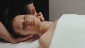 Γυναίκα Brunette που λαμβάνει τη rejuvenating διαδικασία μασάζ λαιμών υγείας στη SPA φιλμ μικρού μήκους