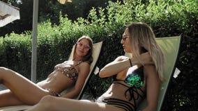 Γυναίκες που κάνουν ηλιοθεραπεία στα κοστούμια λουσίματος σε έναν αργόσχολο ήλιων απόθεμα βίντεο