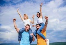 Είμαστε οι νικητές Ευτυχή άτομα piggybacking οι φίλες τους Τα αγαπώντας ζεύγη απολαμβάνουν τη διασκέδαση από κοινού Εύθυμα ζεύγη  στοκ εικόνες