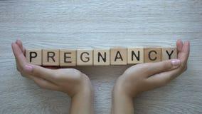 Εγκυμοσύνη, χέρια που ωθούν τη λέξη στους ξύλινους κύβους, οικογενειακός προγραμματισμός και παιδιά απόθεμα βίντεο