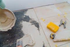 Εγχώρια βελτίωση, tiler εργατών οικοδομών ανακαίνισης κόλλα πατωμάτων κεραμικών κεραμιδιών στοκ εικόνα με δικαίωμα ελεύθερης χρήσης