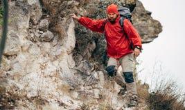 Εικόνα του νέου αρσενικού που στα βουνά που φορούν τα κόκκινα ενδύματα που ερευνούν τη νέα θέση Οδοιπορία και ορειβασία ταξιδιωτι στοκ εικόνες