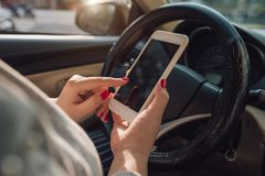 Εικόνα προτύπων του χεριού γυναικών που χρησιμοποιεί το κινητό smartphone με την κενή οθόνη οδηγώντας το αυτοκίνητο και αφήνοντας στοκ εικόνες