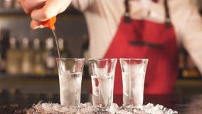Ειδικός μπάρμαν στην κομψή ομοιόμορφη χύνοντας βότκα στα παγωμένα κοντά γυαλιά απόθεμα βίντεο