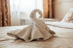 Ειδώλιο του Κύκνου που γίνεται από τις πετσέτες σε ένα κρεβάτι σε ένα δωμάτιο ξενοδοχείου στοκ εικόνα
