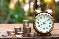 Εκλεκτής ποιότητας χρυσό ξυπνητήρι με τους σωρούς του νομίσματος Χρόνος και χρήματα για την οικονομική έννοια στοκ εικόνα