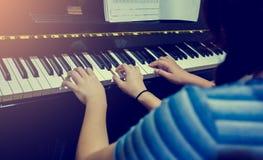 Εκλεκτική εστίαση στην εικόνα της νέας γυναίκας που διδάσκει ένα αγόρι για να παίξει το πιάνο με τη μουσική στοκ φωτογραφία
