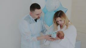 Εκμετάλλευση μητέρων που κοιμάται το νεογέννητο μωρό, ευτυχείς νέοι γονείς που φιλά το παιδί απόθεμα βίντεο