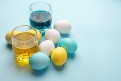 Ελάχιστη έννοια αυγών ζωγραφικής Πάσχα, ζωηρόχρωμα αυγά στο μπλε υπόβαθρο, σύγχρονες διακοπές Πάσχας diy στοκ εικόνα