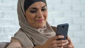 Ελκυστική αραβική γυναίκα που τυλίγει τα κοινωνικά δίκτυα στο smartphone, σύγχρονη τεχνολογία απόθεμα βίντεο
