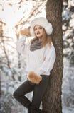 Ελκυστική γυναίκα με την άσπρη γούνα ΚΑΠ και σακάκι που απολαμβάνει το χειμώνα Πλάγια όψη της μοντέρνης ξανθής τοποθέτησης κοριτσ στοκ φωτογραφία