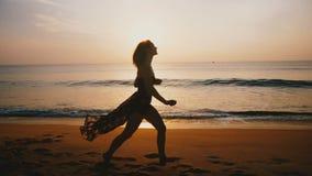 Ελκυστική μέση ηλικίας ευτυχής γυναίκα που τρέχει κατά μήκος της απίστευτης χρυσής παραλίας θάλασσας ηλιοβασιλέματος, της έννοιας φιλμ μικρού μήκους