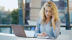Ελκυστική νέα γυναίκα που εργάζεται στην περιοχή στο θερινό καφέ Χρησιμοποιεί το lap-top απόθεμα βίντεο