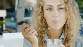 Ελκυστική νέα γυναίκα που τρώει το παγωτό στον καφέ, που χαμογελά στη κάμερα απόθεμα βίντεο