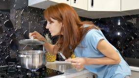 Ελκυστική νέα σύζυγος που υπερασπίζεται τη σόμπα στην κουζίνα, που μαγειρεύει και που μυρίζει τα συμπαθητικά αρώματα από το γεύμα απόθεμα βίντεο
