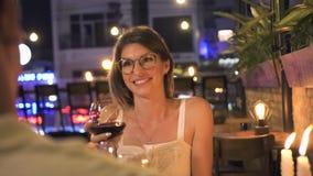 Ελκυστική ομιλούσα φρυγανιά γυναικών ενώ ρομαντικό κρασί γευμάτων και κατανάλωσης στο εστιατόριο Νέο κρασί κατανάλωσης γυναικών α απόθεμα βίντεο