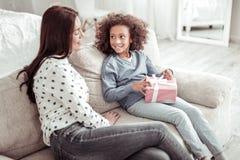 Ελκυστική συμπαθητική συνεδρίαση γυναικών στον καναπέ μαζί με ένα κορίτσι στοκ εικόνες