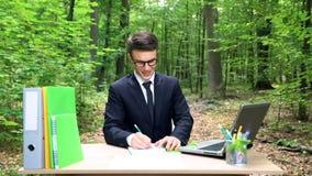Εμπνευσμένος επιχειρηματίας που γράφει τις ιδέες του στο σημειωματάριο, που κάθεται στο γραφείο στο δάσος στοκ φωτογραφία με δικαίωμα ελεύθερης χρήσης