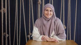 Ενήλικη όμορφη μουσουλμανική γυναίκα με το hijab στο κεφάλι που χαμογελά για τη κάμερα στο δωμάτιο απόθεμα βίντεο