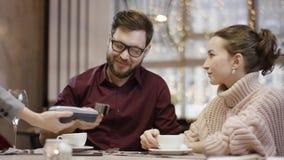 Ενήλικος επιχειρηματίας που χρησιμοποιεί την πληρωμή smartphone σε μια συνεδρίαση εστιατορίων σε ένα εστιατόριο από τον πίνακα με απόθεμα βίντεο