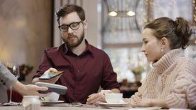 Ενήλικο άτομο που απαιτεί από έναν σερβιτόρο και που πληρώνει το λογαριασμό με τη χρησιμοποίηση της τεχνολογίας NFC στο smartphon απόθεμα βίντεο
