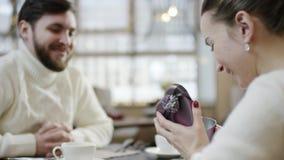 Ενήλικο ευτυχές άτομο χέρι της συζύγου φιλήματός του αφότου ακούει που φαίνεται εσωτερικό το διαμορφωμένο κιβώτιο την έδωσε φιλμ μικρού μήκους