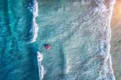 Εναέρια άποψη μιας κολυμπώντας γυναίκας στην μπλε θάλασσα με τα κύματα στοκ φωτογραφίες