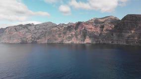 Εναέριος πυροβολισμός Ένας τεράστιος μαύρος-κόκκινος ηφαιστειακός βράχος είναι ένα βουνό στα μπλε νερά του ωκεανού ενάντια στο μπ απόθεμα βίντεο