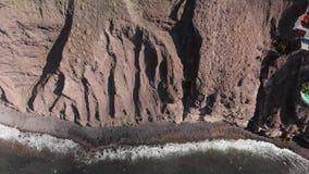 Εναέριος πυροβολισμός Ένας τεράστιος μαύρος-κόκκινος ηφαιστειακός βράχος είναι ένα βουνό στα μπλε νερά του ωκεανού Απότομος βράχο απόθεμα βίντεο