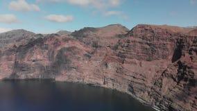 Εναέριος πυροβολισμός Ένας τεράστιος μαύρος-κόκκινος ηφαιστειακός βράχος είναι ένα βουνό στα μπλε νερά του ωκεανού ενάντια στο μπ φιλμ μικρού μήκους