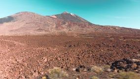 Εναέριος πυροβολισμός κηφήνων Ηφαιστειακό Αριανό τοπίο ερήμων στο κόκκινο Πέτρες και ένα βουνό με ένα ηφαίστειο ενάντια στο μπλε φιλμ μικρού μήκους